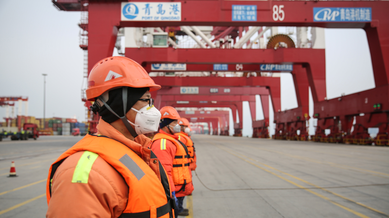 Workers at the port of Qingdao wearing anti-coronavirus masks STR/AFP via Getty Images