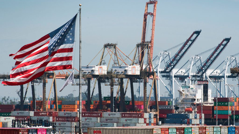 US flag flying in front of containers and cranes at Los Angeles port: credit Mark Ralston/AFP via Getty Images