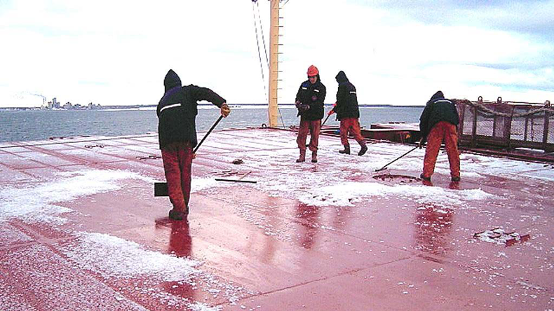 Seafarers clearing ice off a deck