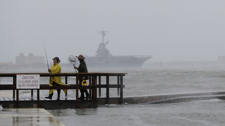 Fishermen walk along a pier as the early bands of Hurricane Harvey make landfall, Friday, Aug. 25, 2017, in Corpus Christi, Texas. Harvey intensified into a hurricane Thursday and steered for the Texas coast with the potential for up to 3 feet of rain, 125 mph winds and 12-foot storm surges in what could be the fiercest hurricane to hit the United States in almost a dozen years.