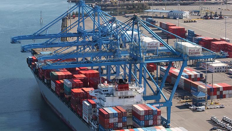A container vessel and cranes at Seaport Alliance's Husky Terminal