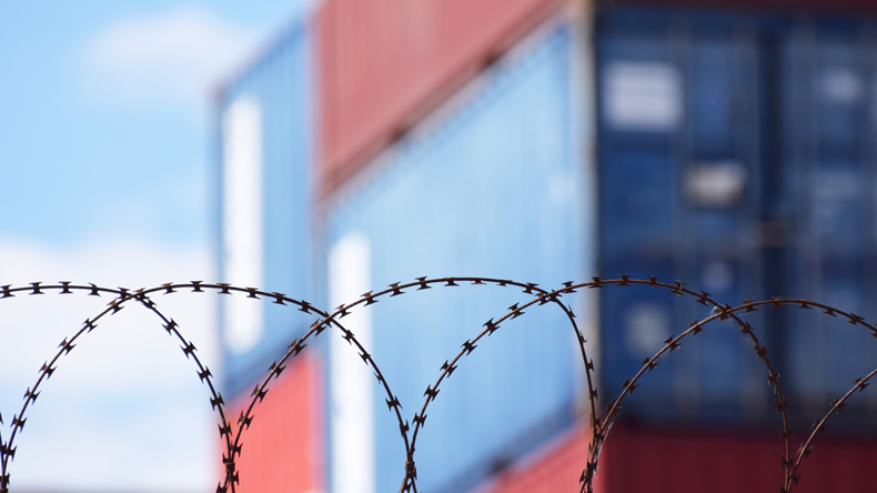 Containers behind barbed wire. Shutterstock.com